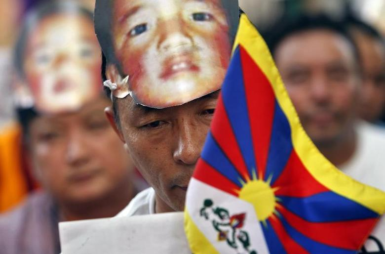 A Tibetan wearing a mask of Gedhun Choekyi Nyima during a protest. May 17 2013 (Photo - Reuters)