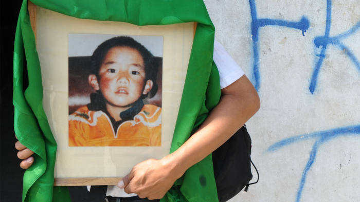 A man carries a portrait of the 11th Panchen Lama. Photo-Financial Times