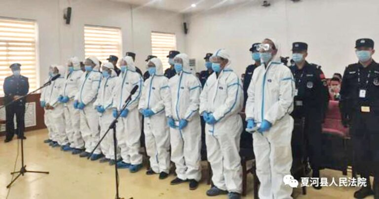 Line up of the 10 defendants in hazmat suit (Photo- Handout)