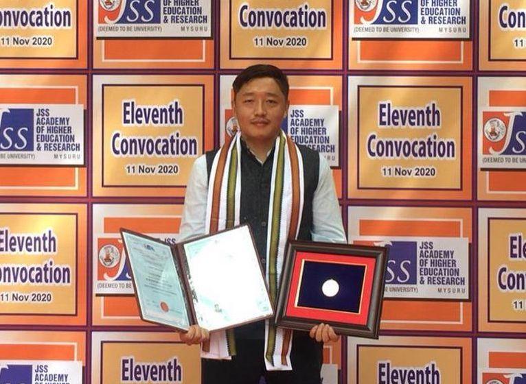 Pema Gyaltsen holding the medal at JJS University in Mysore (Phayul Photo)