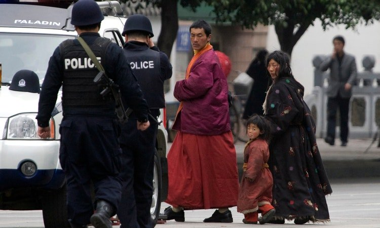 Police patrols passes by a Tibetan family in occupied-Tibet. Photo-Thenewlensinternational