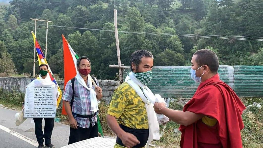 The three activists being felicitated by a monk at the beginning of the 'Peace March' on Wednesday (Phayul photo)
