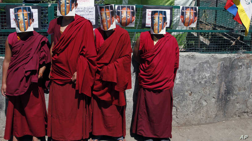 Tibetan monks in exile wear masks depicting the 11th Panchen Lama (Photo courtesy- VOA)